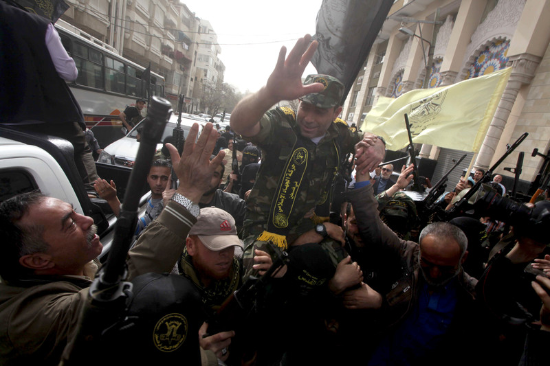 Man wearing military fatigues waves as he is carried by crowd bearing guns and flags