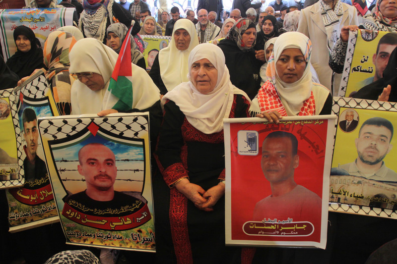 Elderly woman sits amongst crowd holding posters of Palestinian prisoners