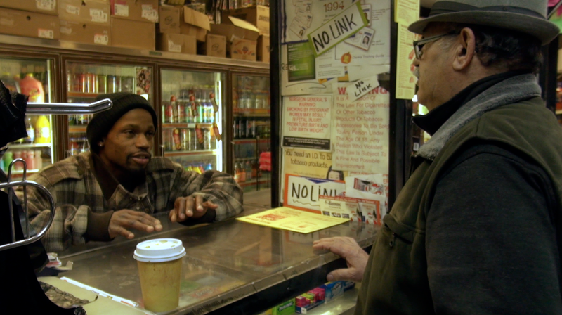 Young African American man talks to store owner with a tall counter separating them