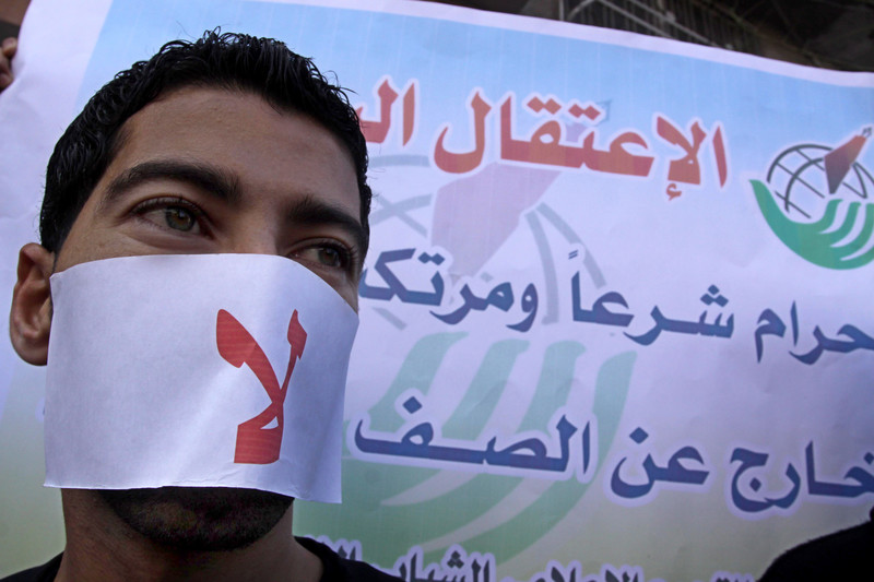 Close-up of man wearing mask over his mouth that says the word no in Arabic in front of press freedom campaign banner