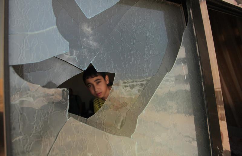 Boy peers through broken window