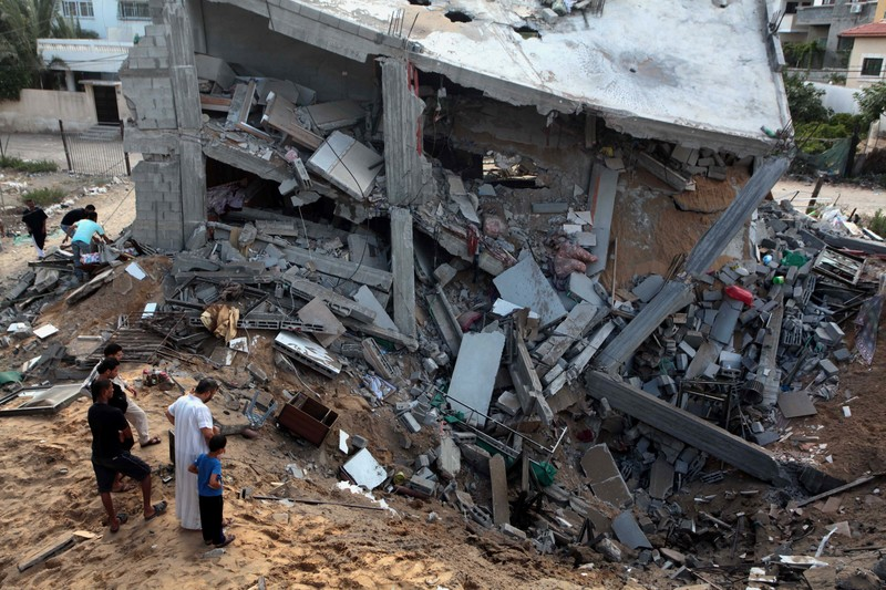Landscape view of Palestinians observing multi-story residence bombed into a crater