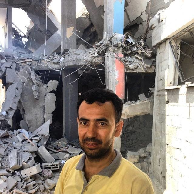 Raed Issa standing beside the apartment block that was previously his home, and that of eight other households