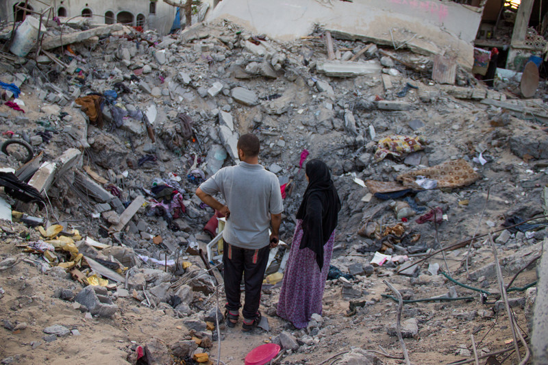 Man and woman look at bombed-out crater where home once stood