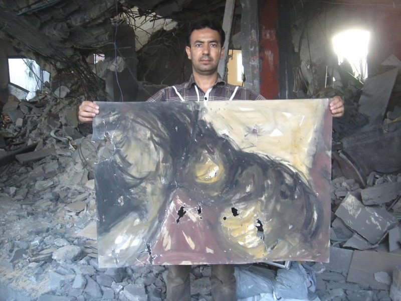 Artist Raed Issa holds up one of his damaged paintings in his bombed-out house in Gaza. (Photos courtesy of Raed Issa)