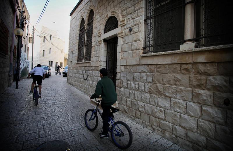 Boys ride bicycles through old neighborhood of Tarshiha