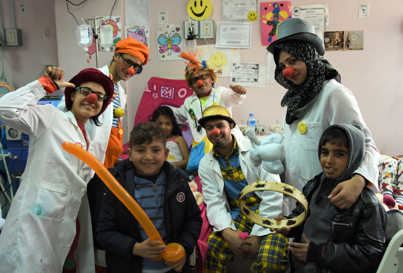 Men and women in silly hats and wigs wearing red foam noses pose with children in hospital room
