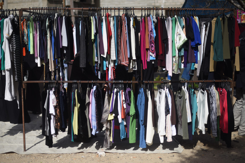 A rack of used clothing in an open-air market
