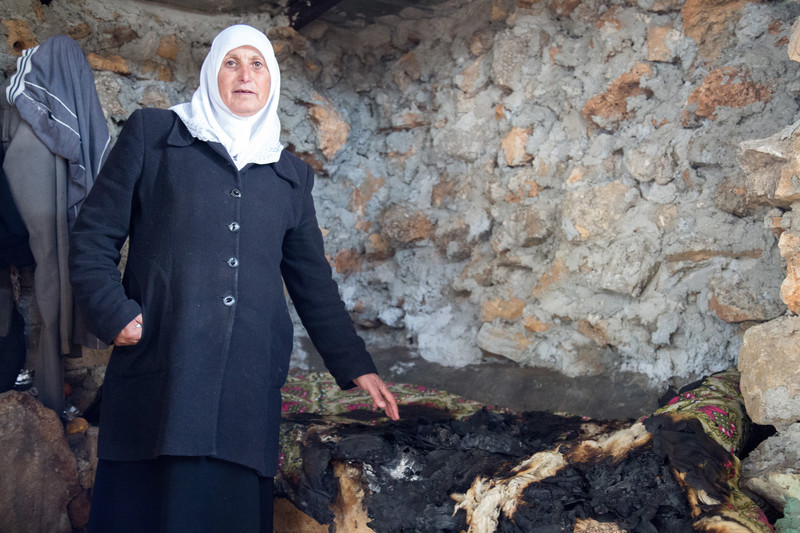 Woman stands in burned-out room