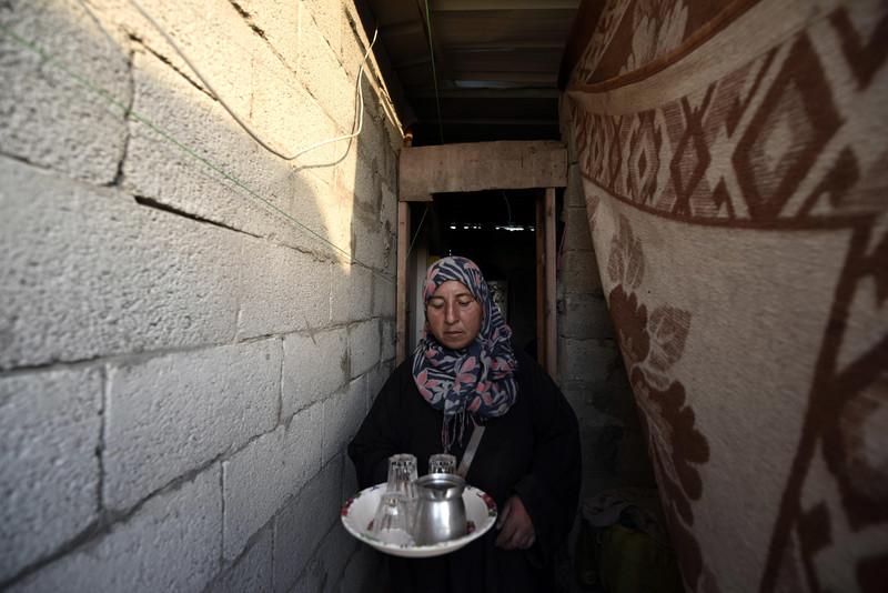 Woman carries tray through narrow corridor