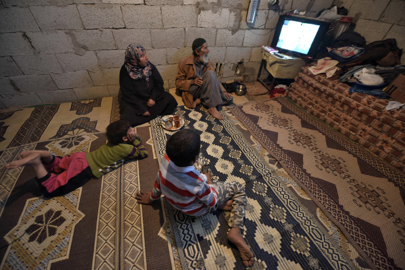 Man, woman and two boys sit on floor and look at a television