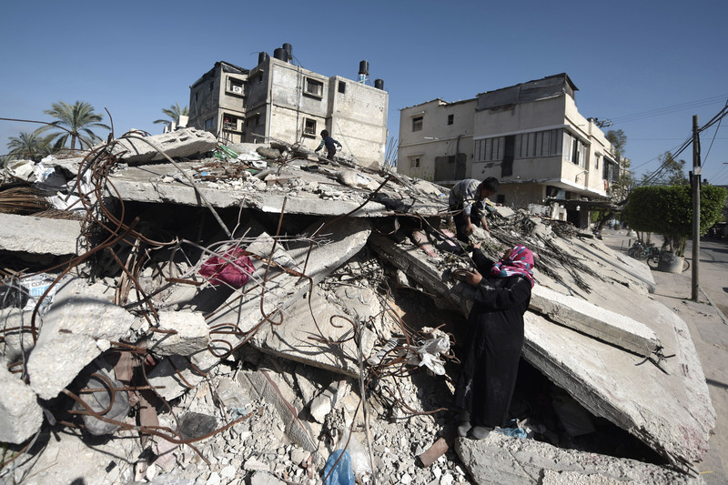 Children climb on pile of rubble as woman looks on