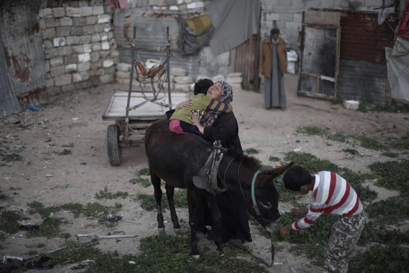 Woman embraces boy sitting on donkey