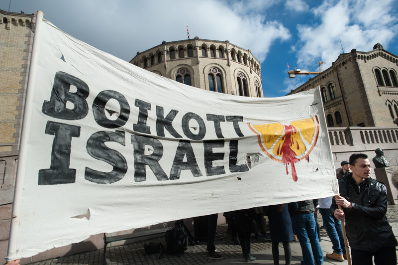 A large banner reading Boikott Israel with an image of a blood-splattered orange slice is held in front of a building