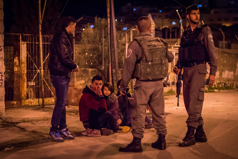 Two armed soldiers stand in front of three Palestinians, including girl, huddled on ground and another standing up