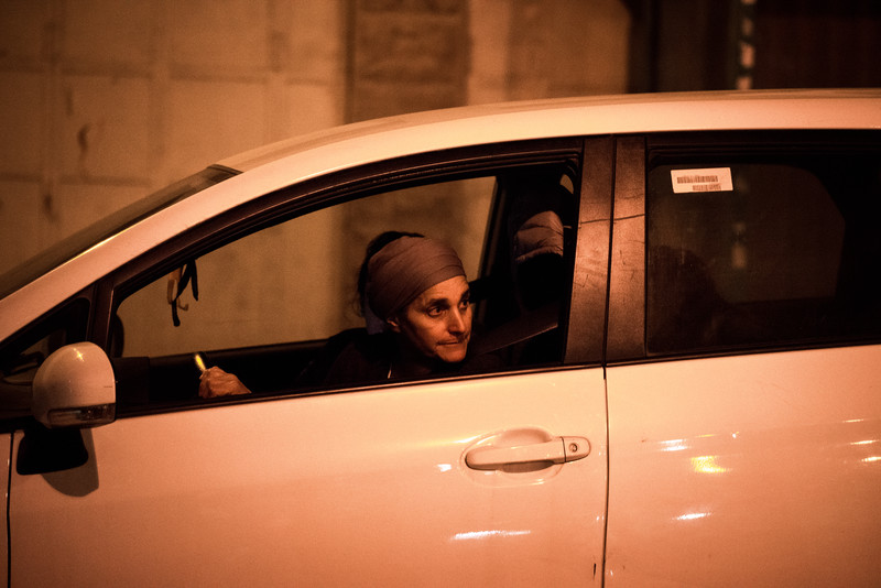 Woman driving car looks out of driver's side window