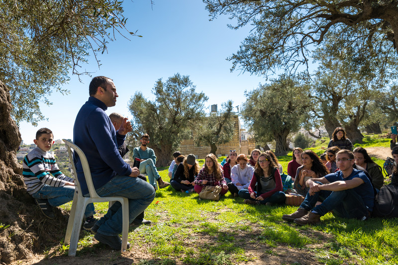 Man sits on chair in front of audience of young people sitting on grass