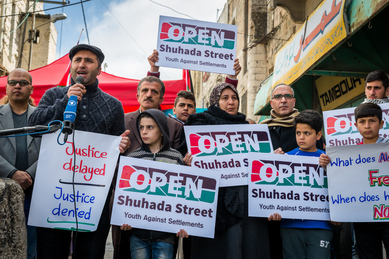Man speaks into microphone accompanied by men, women and children holding signs reading Open Shuhada Street