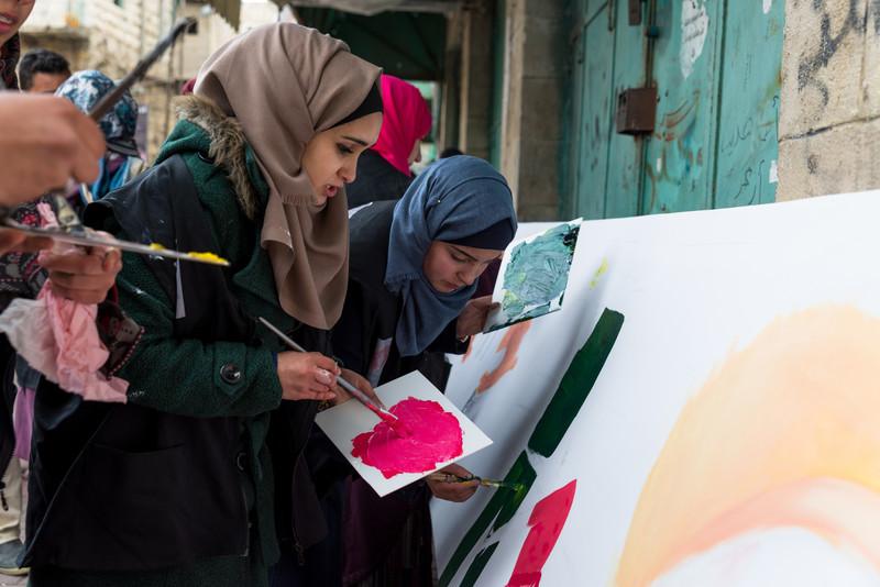 Young women paint a mural