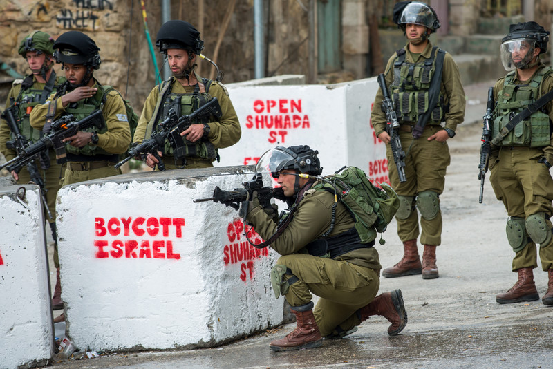Israeli soldiers carrying arms take position behind concrete blocks reading Boycott Israel Open Shuhada Street