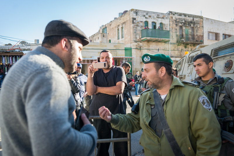 Man in beret argues with soldier as another man films