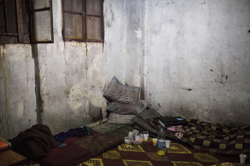 View of corner of room with rust-stained walls and pillows and mats piled on floor