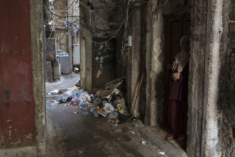 Woman stands in doorway in narrow alleyway strewn with trash