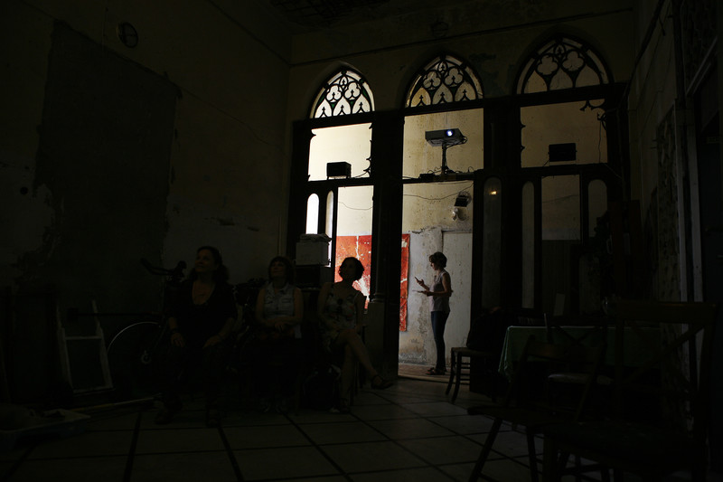 Silhouetted figures stand in arched doorways