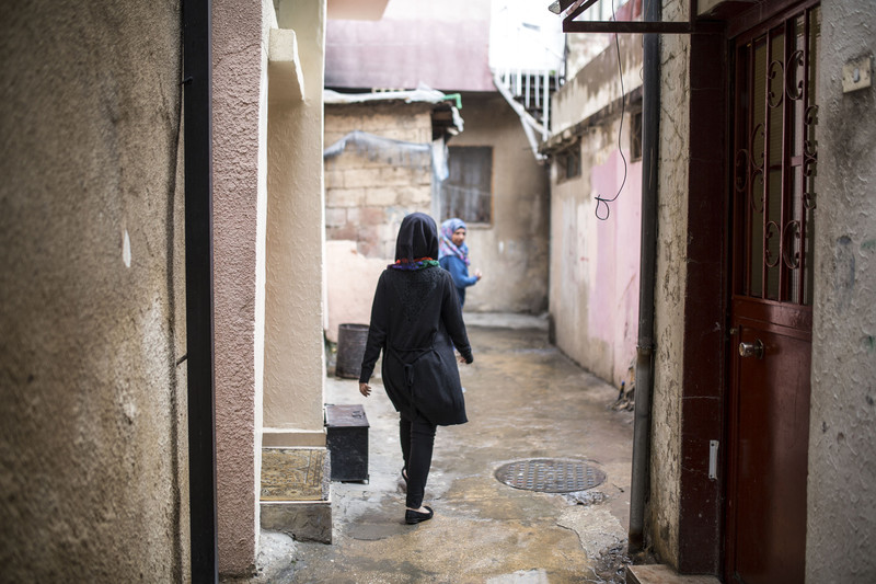 View of young woman's back as she walks in camp alleyway with another woman in front of her