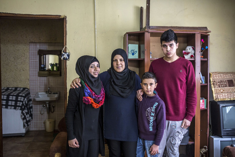 Smiling young woman stands next to woman and two boys in a family room