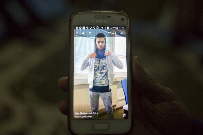 Close-up of phone displaying image of youth