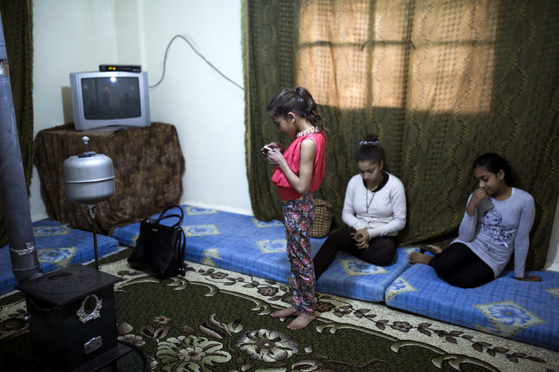 Girl stands in middle of room looking at device as two older girls sit on mats on floor in living room