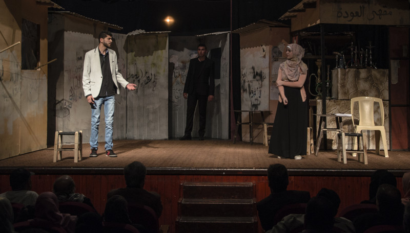 Young man and woman appear on stage as audience sits in foreground
