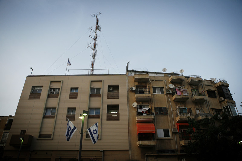 View of plain building with large antenna on top and Israeli flags hanging in front