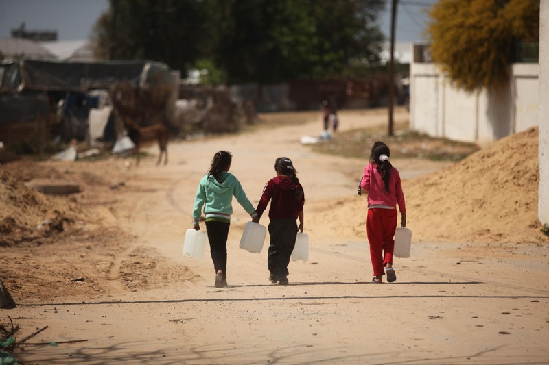 Three children carry large containers of water as they walk along a dirt road