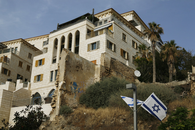 Large luxury building next to old stone wall with Israeli flags hanging in front of it