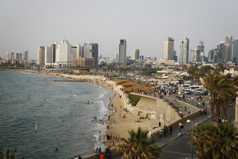 Landscape view of sea and beach surrounded by city skyline