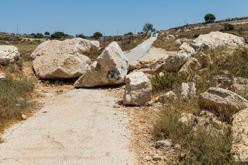 Large boulders block dirt road