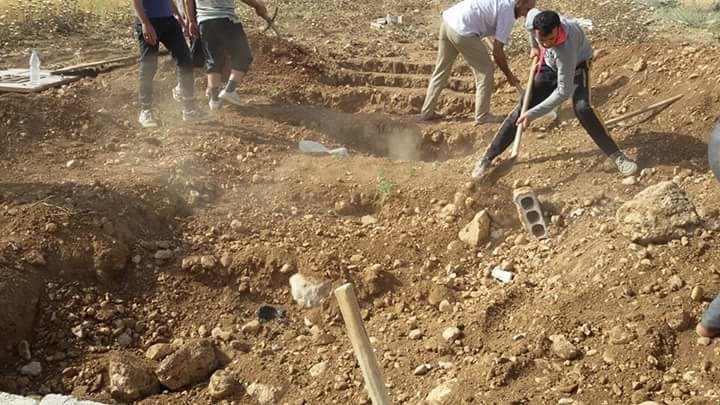 Young men dig shallow graves
