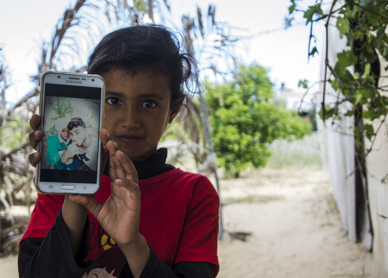 Girl displays a mobile phone showing a photo of older woman and youth