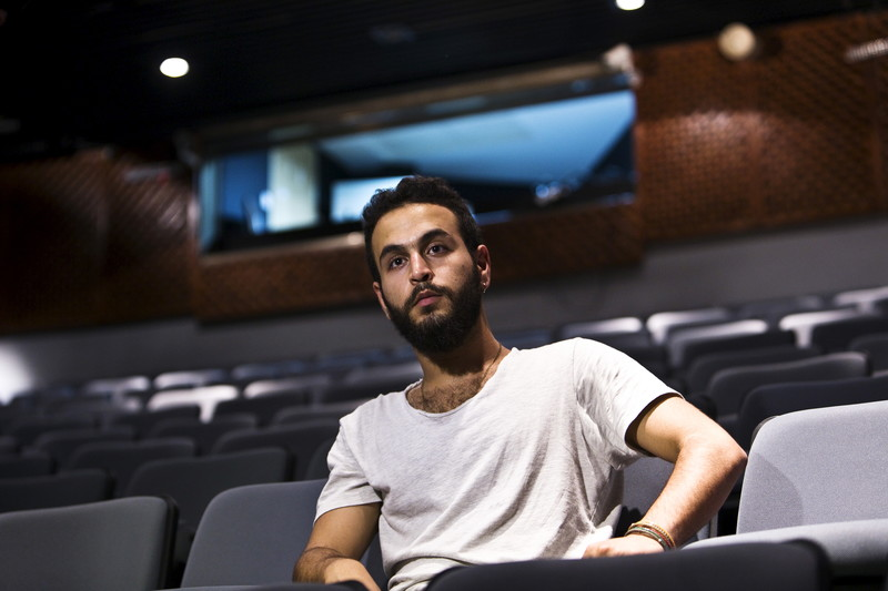 Young man sits in row of empty seats in theater