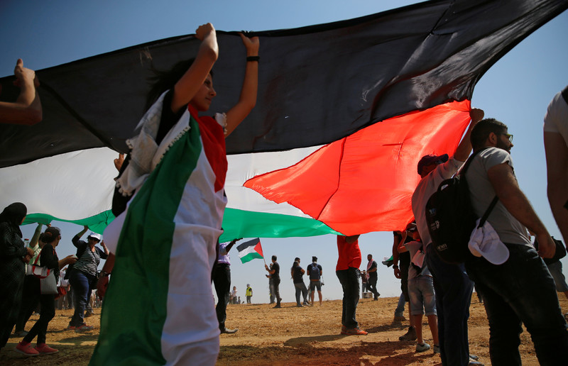 Young people hold large Palestinian flag