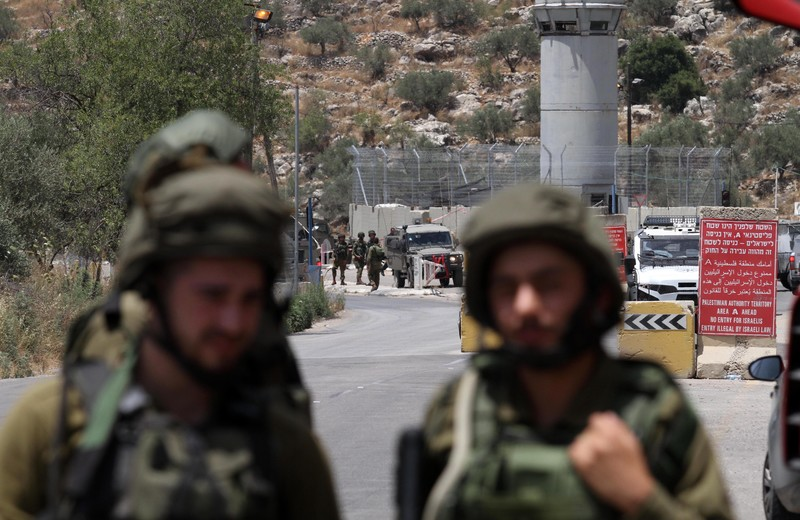 Israeli soldiers stand in foreground with military checkpoint watchtower and crowd of people in background