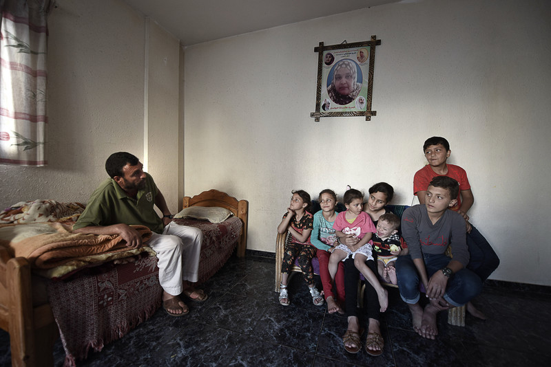 Man sits on small bed as seven children gather on a couch underneath a poster of woman