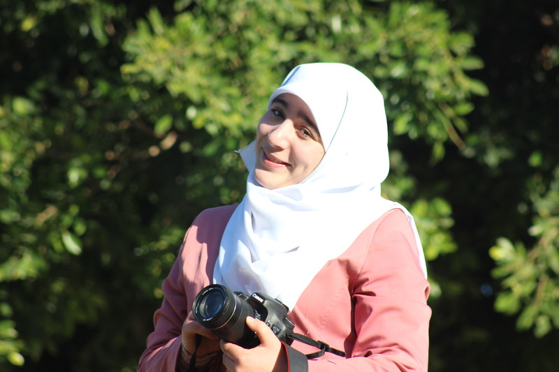 Smiling young woman holds camera while standing in front of trees