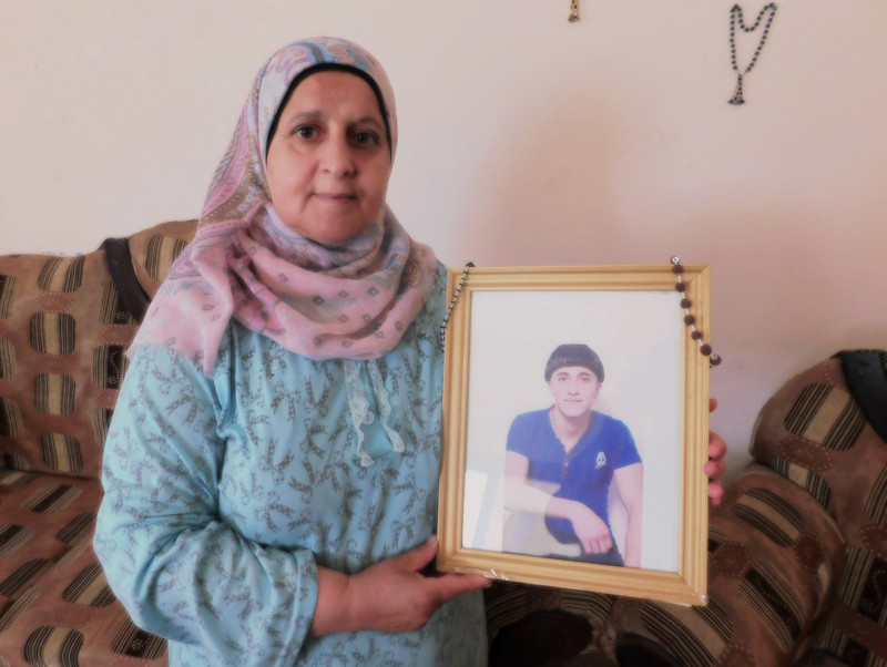 Woman holds framed photograph of teenage boy