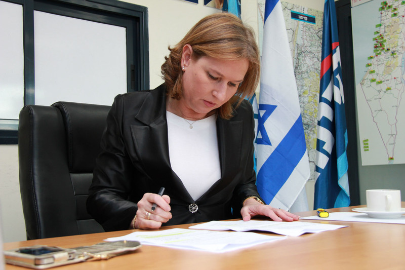 Tzipi Livni sits at desk looking at paper with an Israeli flag hanging behind her