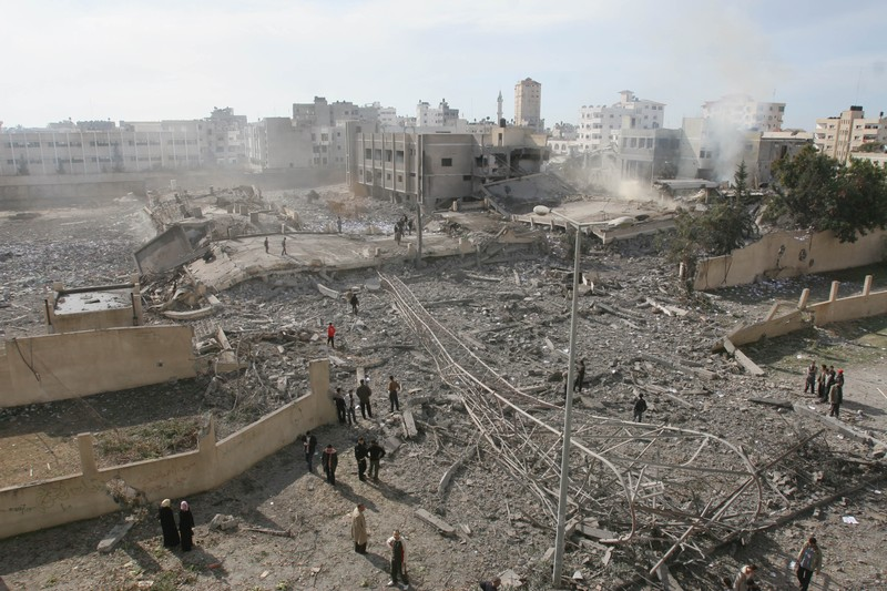 Landscape view of neighborhood flattened by bombing and dust rising up from ruins