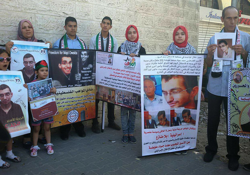 Adults and children carry posters calling for freedom for Majd Oweida