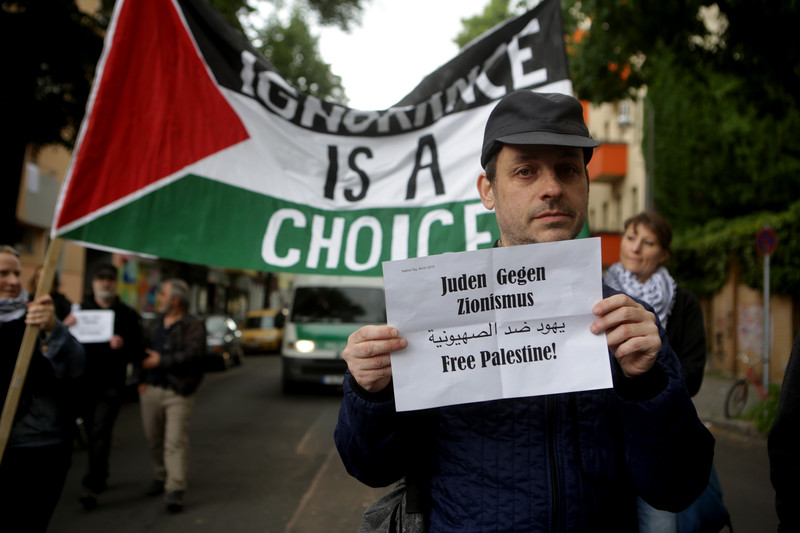 Man carries sign reading Jews against Zionism in German and Arabic and Free Palestine in English